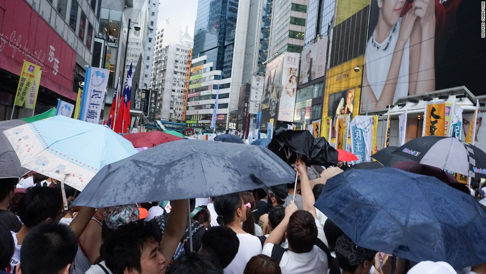 As rain begins to come down on the protesters, umbrellas fly open.
