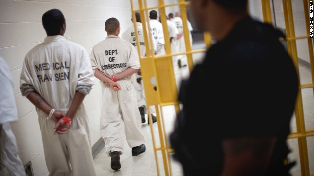 A guard looks on at right as prisoners move through the state prison Thursday, March 3, 2011 in Jackson, Georgia.