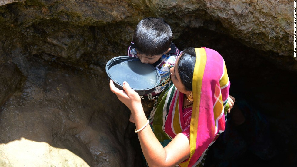 A woman offers drinking water from a well to her son in Surendranagar on June 1.