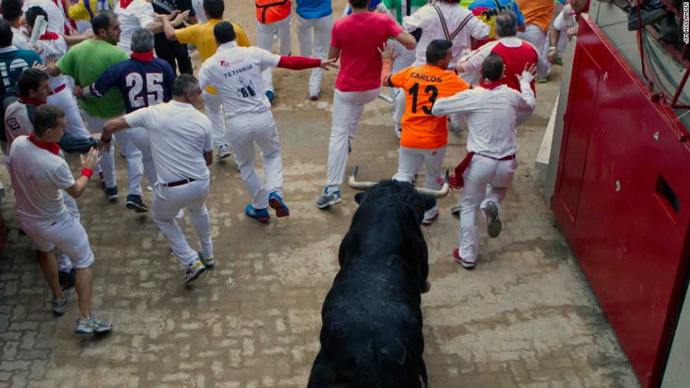 Runners enter the bullring in Pamplona ahead of a lone fighting bull in the eight-day Fiesta de San Fermin on July 12, 2013.