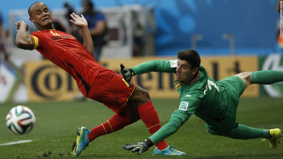 Belgium defender and captain Vincent Kompany, left, and Belgium's goalkeeper Thibaut Courtois eye the ball.