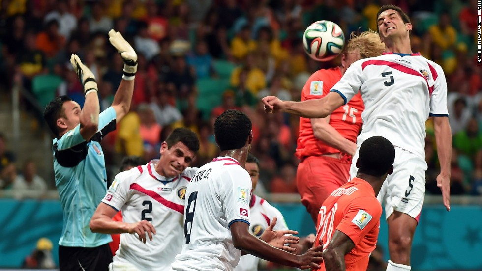 Netherlands forward Dirk Kuyt, second right, heads the ball marked by Costa Rica's midfielder Celso Borges.