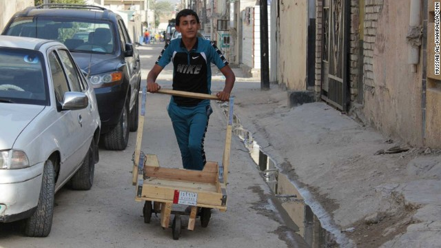 Mustafa, 15, pushes a trolley he uses in his day job transferring goods across the area to help support his family.