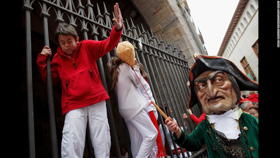 A child is playfully hit July 7 during the Giants and Big Heads Parade, which is also a traditional part of the San Fermin festival.
