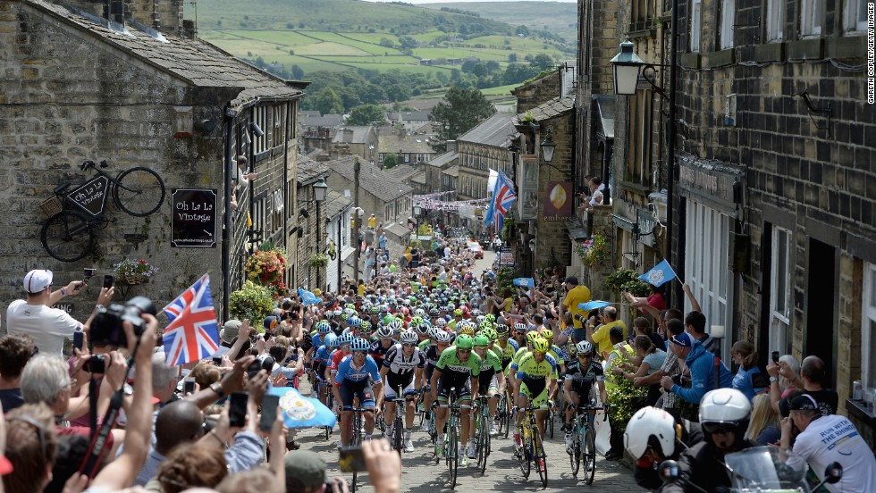 The peloton rides through a street in Haworth, England, during Stage 2 of the Tour de France on Sunday, July 6. The legendary road race ends in Paris on July 27.