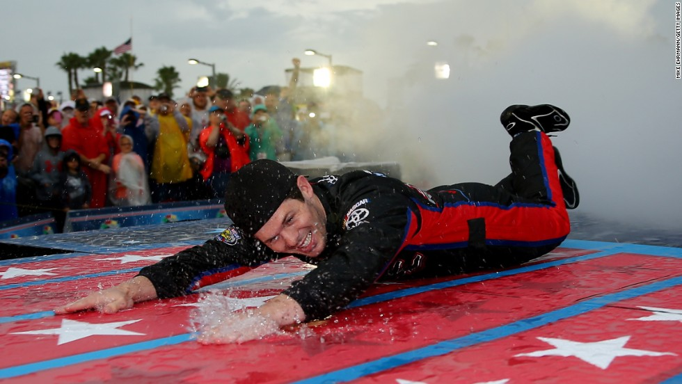 NASCAR driver Ryan Truex slides down a wet stage during driver introductions for the Coke Zero 400 on Saturday, July 5, in Daytona Beach, Florida. The Sprint Cup race at Daytona International Speedway was delayed and then shortened because of rain. Aric Amirola was named the winner after 112 laps of the 160-lap race.