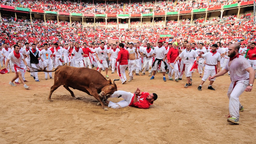 A reveler is pushed by a bull in the bull ring on Tuesday, July 8.