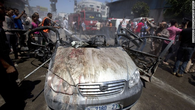 Firefighters extinguish a vehicle targeted in an Israeli airstrike on Gaza City on July 8, 2014.