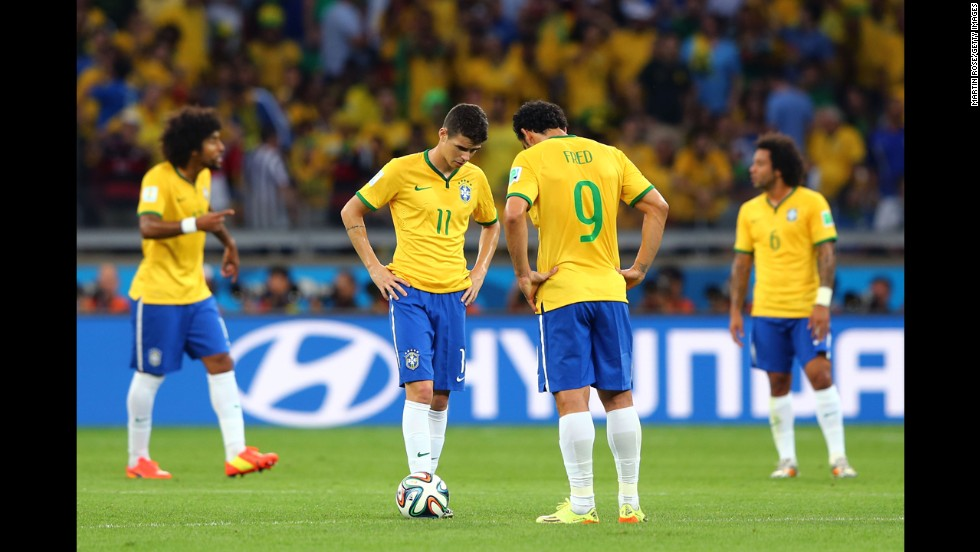 Brazilian players Oscar and Fred hang their heads after a German goal.