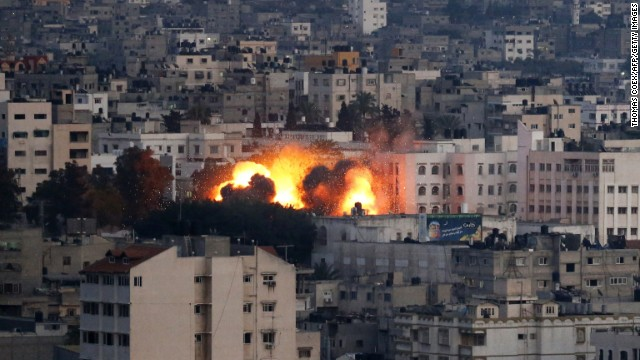 Flames erupt from a building hit by an Israeli air strike on July 9, 2014 in Gaza City. Israeli warplanes pounded Gaza today, killing at least 24 people in a major new confrontation with Palestinian militants, as Hamas flexed its firepower and sent thousands running for shelters across the country. AFP PHOTO / THOMAS COEX (Photo credit should read THOMAS COEX/AFP/Getty Images)