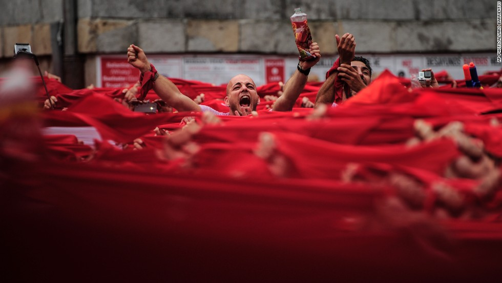 "JULY 10 - PAMPLONA, SPAIN: Revelers hold red kerchiefs during the launch of the ""Chupinazo"" rocket, to mark the official opening of the 2014 San Fermin festival. The running of the bulls was glorified in <a href=""http://edition.cnn.com/2014/07/07/opinion/pamplona-bulls-hemingway/"">Ernest Hemingway's 1926 novel ""The Sun Also Rises.""</a>"