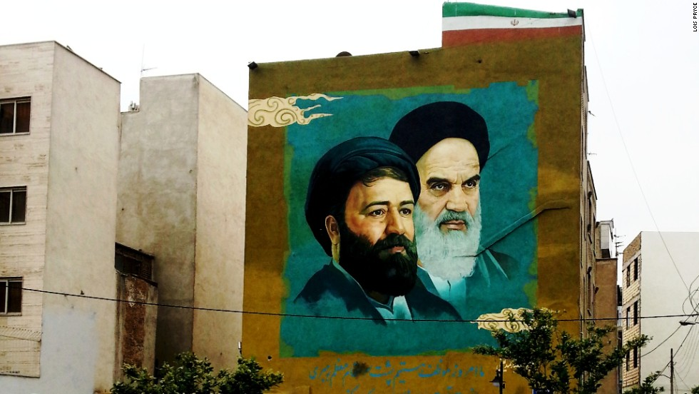 "Murals, posters and banners of Iran's Supreme Leader <a href=""http://edition.cnn.com/2012/12/30/world/meast/ayatollah-seyyed-ali-khamenei---fast-facts/"">Ayatollah Seyyed Ali Khamenei</a> and Imam Khomeini loom over streets, parks and public buildings."