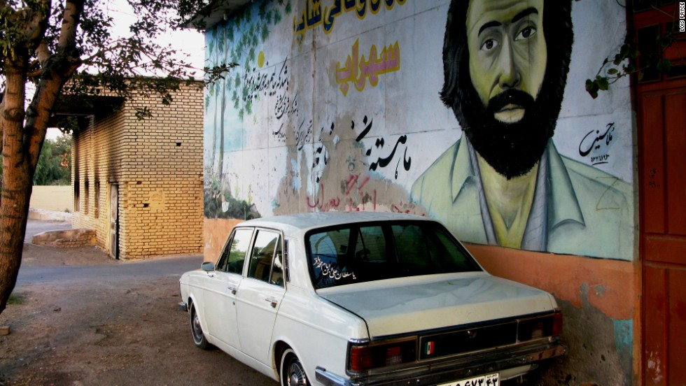 "Two common sights of Iran: murals of the war ""martyrs"" and the ubiquitous Paykan, a vehicle also known as the Iranian chariot."