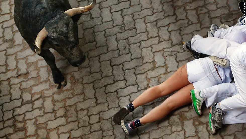 Revelers lie on the ground as a bull runs by July 13.
