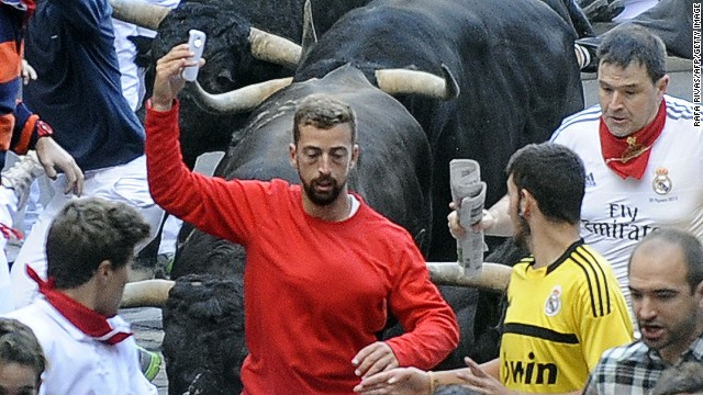 A participant runs in front of Jandilla's bulls as he takes a 'selfie' (photograph of himself) during the fifth bull-run of the San Fermin Festival in Pamplona, northern Spain, on July 11, 2014. Spanish authorities are cracking down on dare devils who shoot camera footage even as they risk their lives by running with half-tonne fighting bulls at the annual San Fermin festival. PHOTO/ RAFA RIVAS (Photo credit should read RAFA RIVAS/AFP/Getty Images)