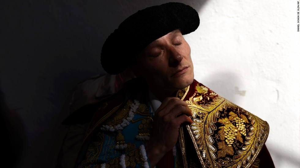 "Bullfighter Diego Urdiales adjusts his capote before doing the ""paseillo,"" or ritual entrance to the arena, before a bullfight on Sunday, July 13."
