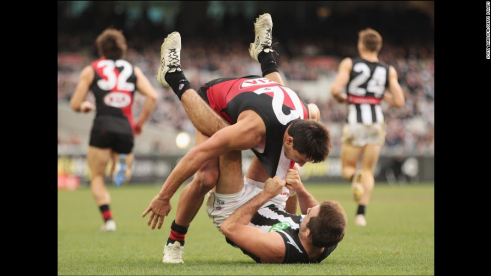 Steele Sidebottom of the Collingwood Magpies, bottom, and Mark Baguley of the Essendon Bombers wrestle during an Australian Football League match Sunday, July 13, in Melbourne.