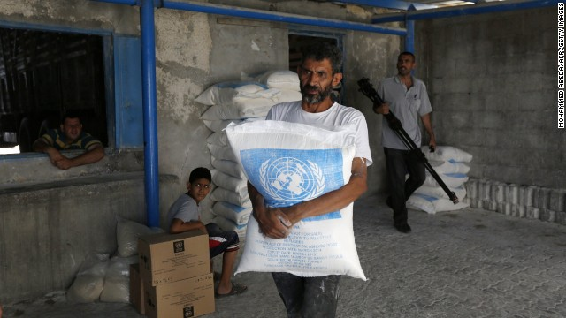 A Palestinian man carries a bag that he received at an aid distribution centre of the United Nations Relief and Works Agency (UNRWA) on July 14, 2014 in Gaza City.
