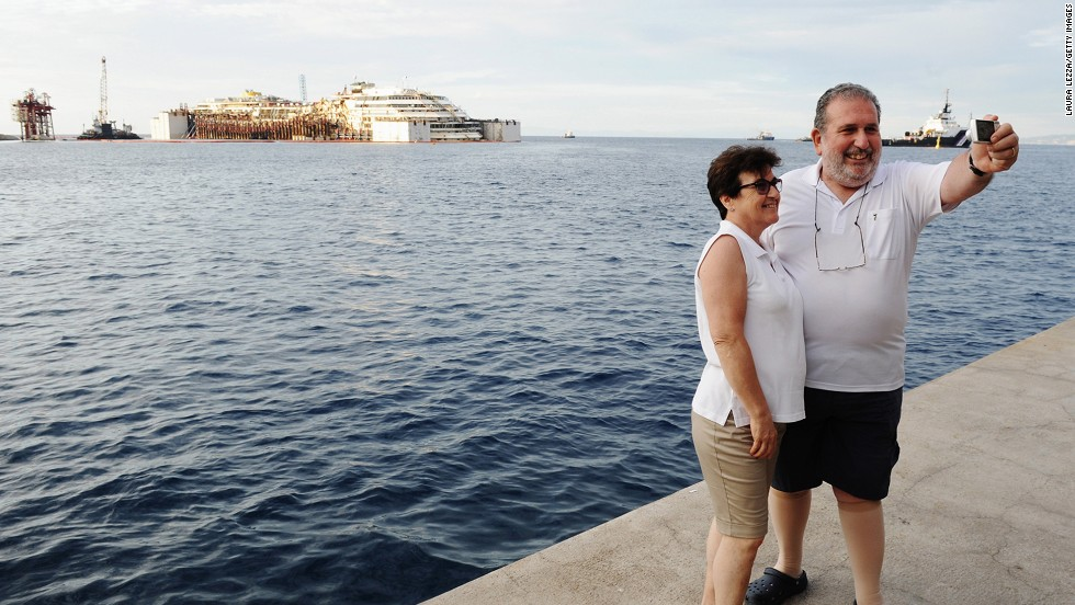 People snap a photo Monday, July 14, near the Costa Concordia, the cruise liner than ran aground and sank off the coast of Italy two and a half years ago. The ship is now being re-floated so that it can be towed away from the Italian island of Giglio.
