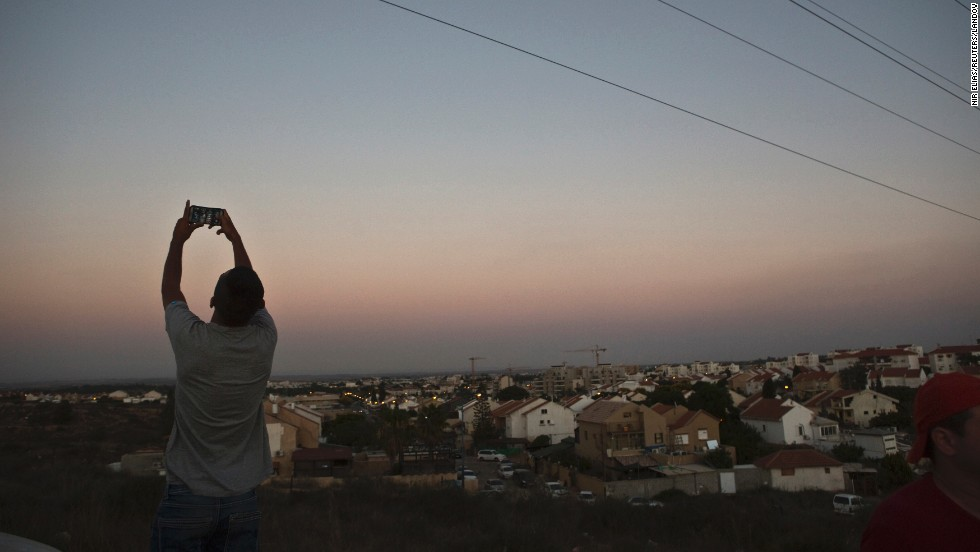 With Gaza in the background, an Israeli teen takes a selfie on a hill near Sderot, Israel, on Sunday, July 13. Hostilities between Israel and Palestinian militants escalated this month after the killing of three Israeli teenagers and a Palestinian teen.