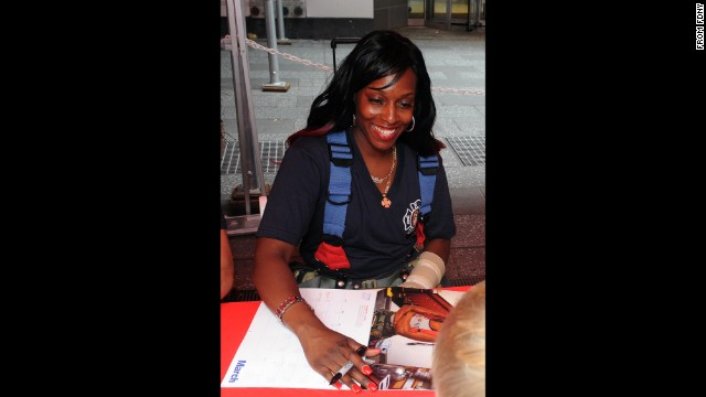 Danae Mines signs a copy of the 2015 FDNY Calendar of Heroes.