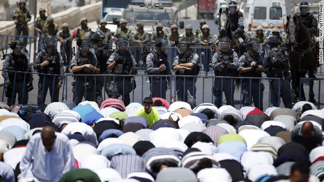 Israeli police stand guard as Muslim men pray in the street outside the Old City in East Jerusalem on July 4.