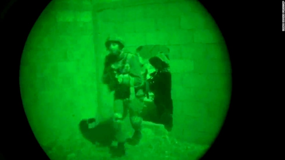 This image, made from video shot through a night-vision scope, was released by the Israeli military on July 18. It shows troops moving through a wall opening during the early hours of the ground offensive in Gaza.
