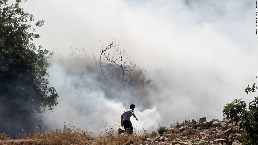 A Palestinian demonstrator, protesting Israel's military operation in Gaza, runs through smoke July 18 during clashes with Israeli soldiers at the entrance of the Ofer prison in the West Bank village of Betunia.