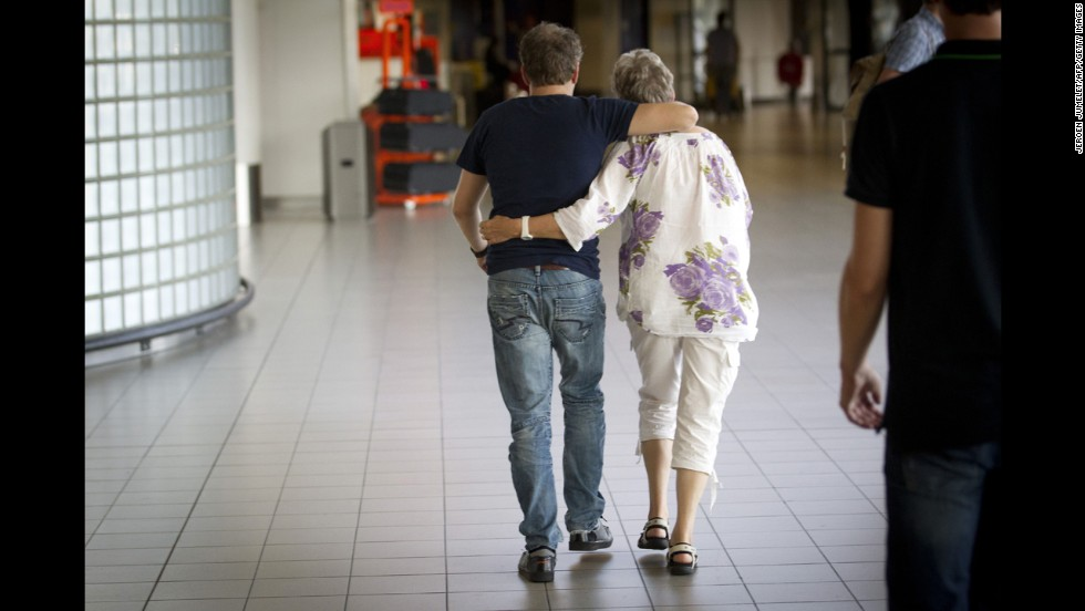 A couple walks through Schiphol Airport to a location where more information will be given regarding the flight on July 17, 2014.