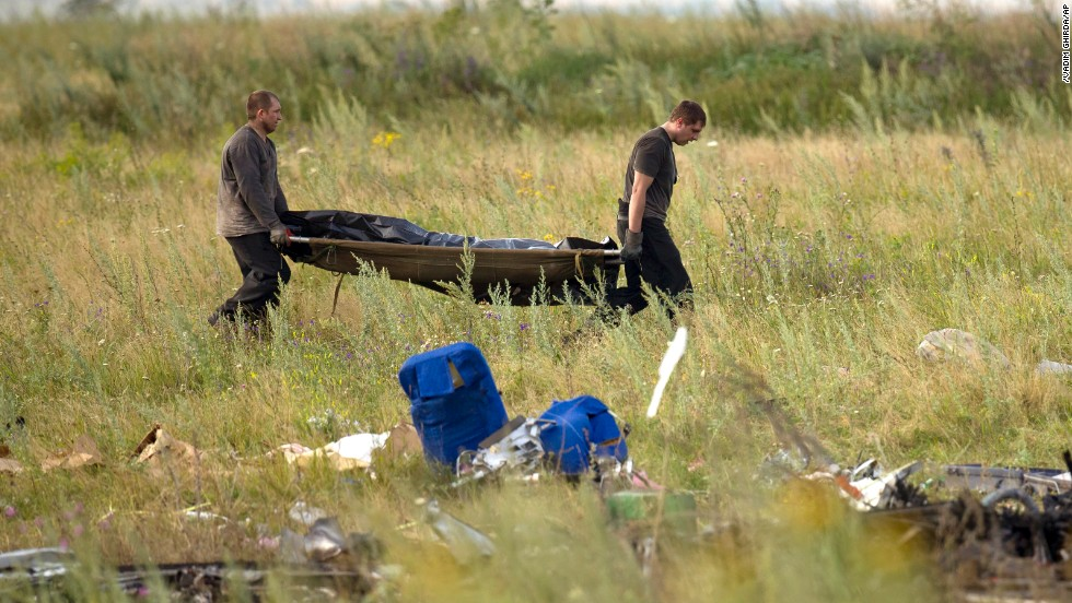 Emergency workers carry the body of a victim at the crash site on July 19, 2014.