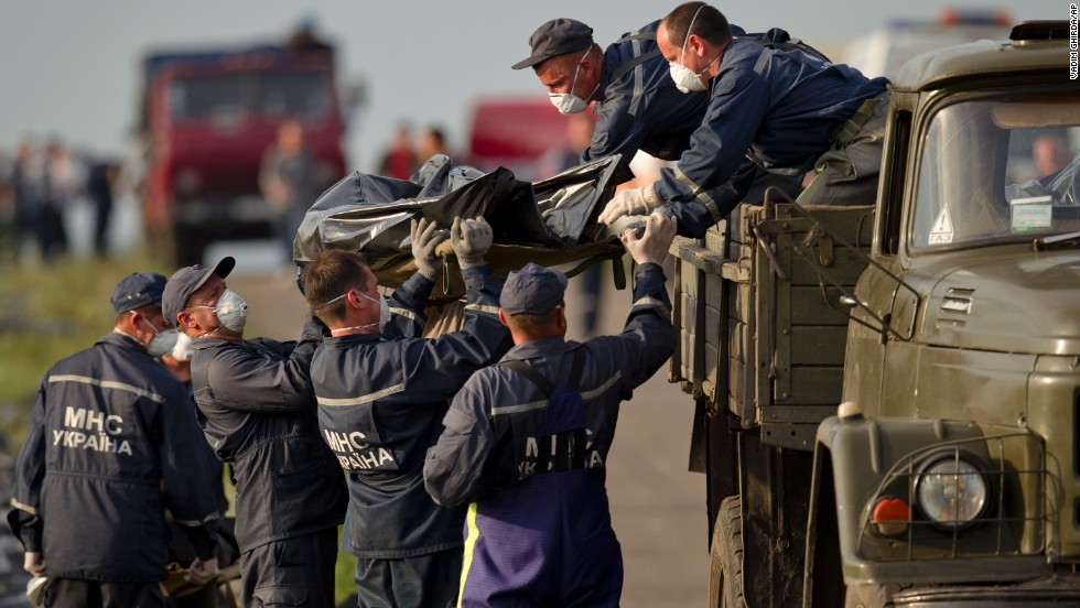 Emergency workers load the body of a victim onto a truck at the crash site on Saturday, July 19, 2014.