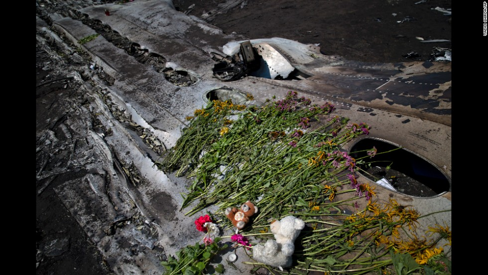Toys and flowers sit on the charred fuselage of the jet as a memorial on July 20, 2014.
