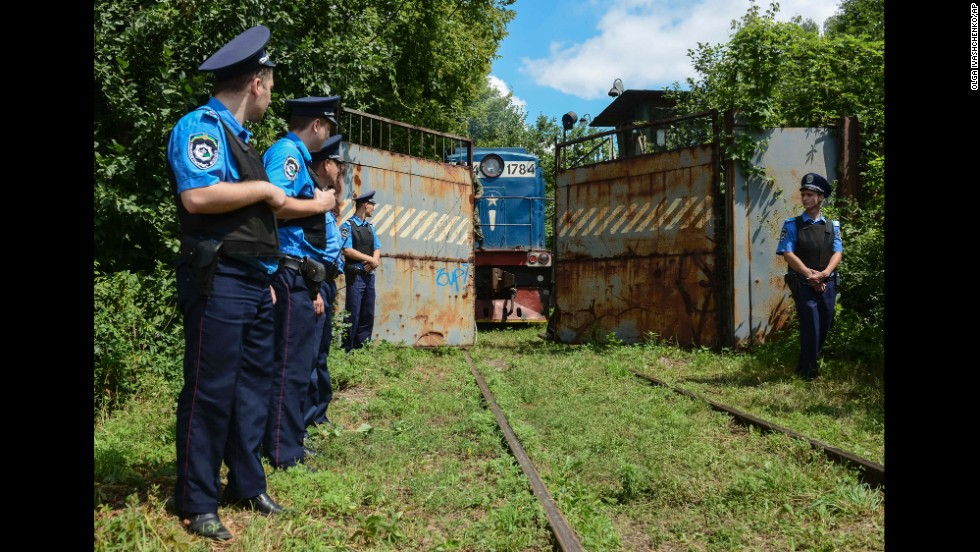 Police officers secure a refrigerated train loaded with bodies as it arrives at a Kharkiv factory on Tuesday, July 22.