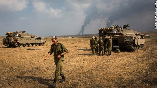 Israeli soldiers stand near their tank while smoke due to airstrikes and shelling rises from Gaza on July 22, 2014 near Sderot, Israel.