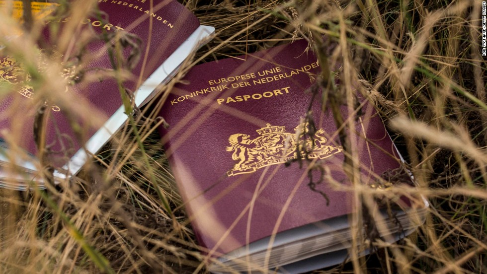 Two Dutch passports belonging to passengers lie in a field at the site of the crash on Tuesday, July 22.