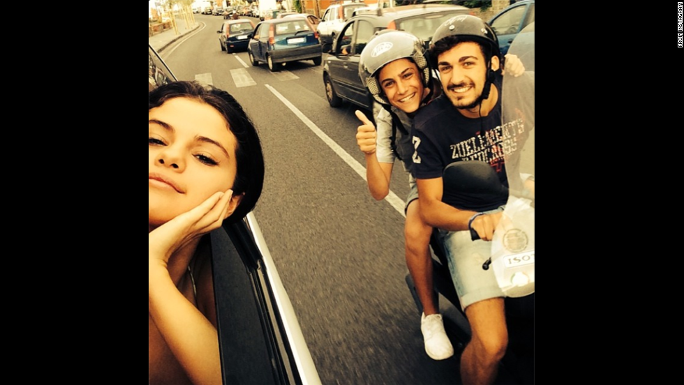 "Actress and singer Selena Gomez poked her head out of her vehicle to take a selfie with two fans in Italy on Friday, July 18. The photo was posted <a href=""http://instagram.com/p/qmYk8FujGq/"" target=""_blank"">on her Instagram account</a> with the message: ""I told them I would :)"""