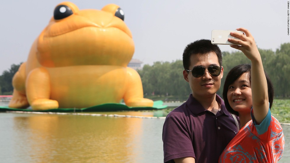 People take photos in front of a large golden fabric frog Saturday, July 19, in Beijing's Yuyuantan Park. The frog, which is 22 meters (72 feet) tall, is based on the golden frog that symbolizes luck and is thought to bring wealth and fortune in traditional Chinese culture.