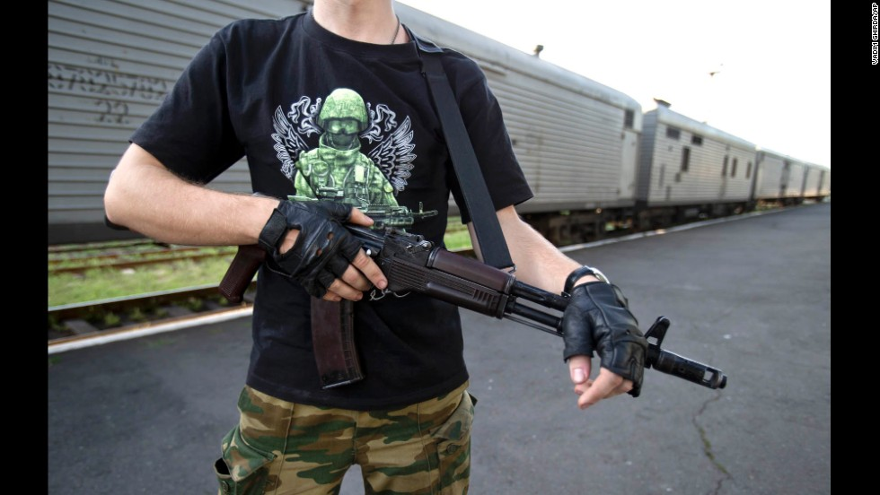 An armed pro-Russian rebel stands guard next to a refrigerated train in Torez, Ukraine, on Sunday, July 20.