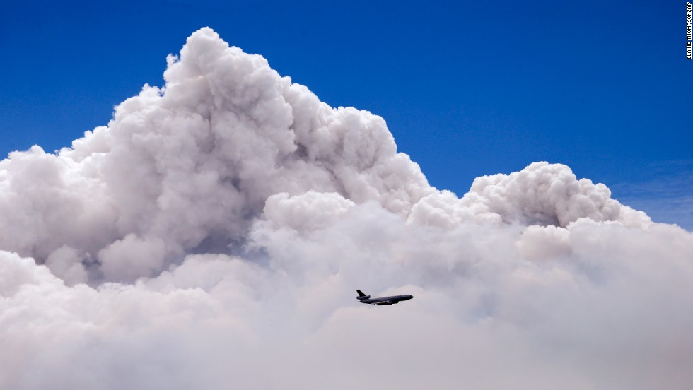 A plane is dwarfed by the tip of a rising smoke cloud as it prepares to drop fire retardant over a wildfire near Carlton, Washington, on Saturday, July 19.