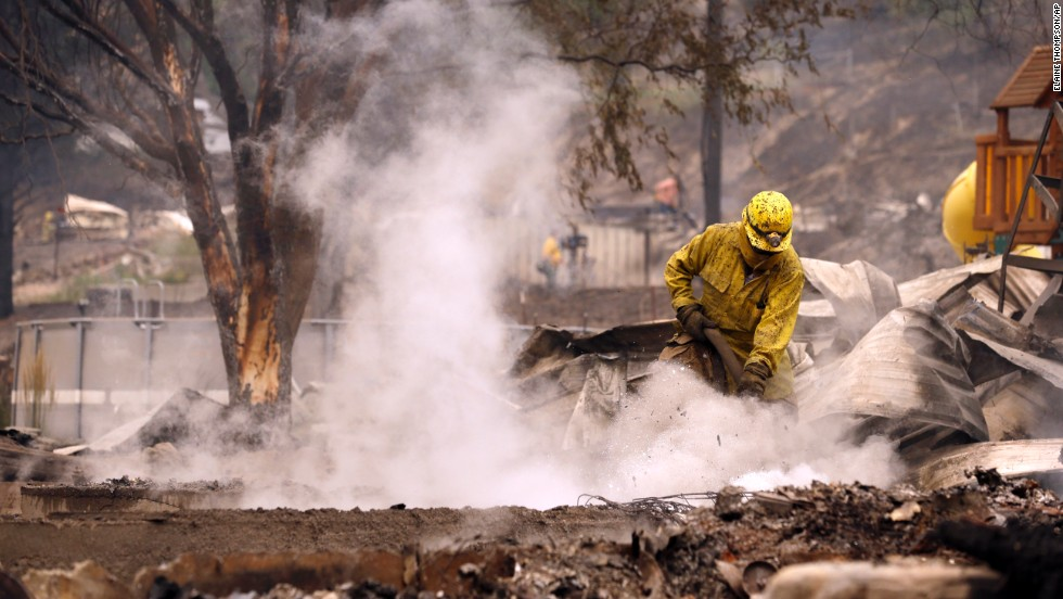 A firefighter works on the still-smoldering home of Pateros Mayor Libby Harrison on July 18.