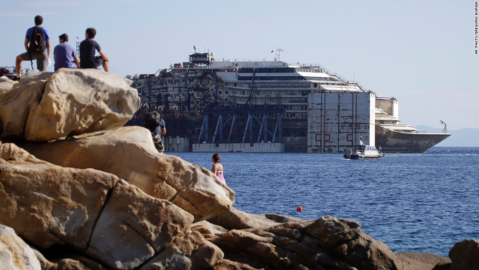 "JULY 23 - GIGLIO, ITALY: <a href=""http://cnn.com/2014/07/23/world/europe/costa-concordia-leaves-behind/index.html"">The wreck of the Costa Concordia cruise ship </a>is towed away from the tiny Tuscan island of Giglio. More than two years after it crashed into a reef and capsized, the ship has begun its final journey to the Italian port of Genoa, where it will be scrapped."