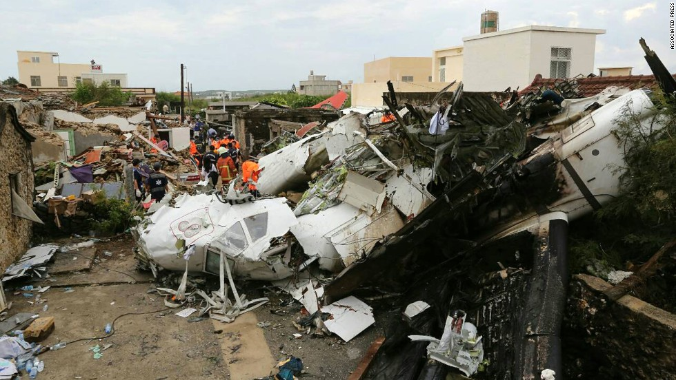 Rescue workers survey the wreckage of the flight on Thursday, July 24. The plane was attempting to land in stormy weather but crashed on the island late Wednesday, wrecking houses and cars on the ground.