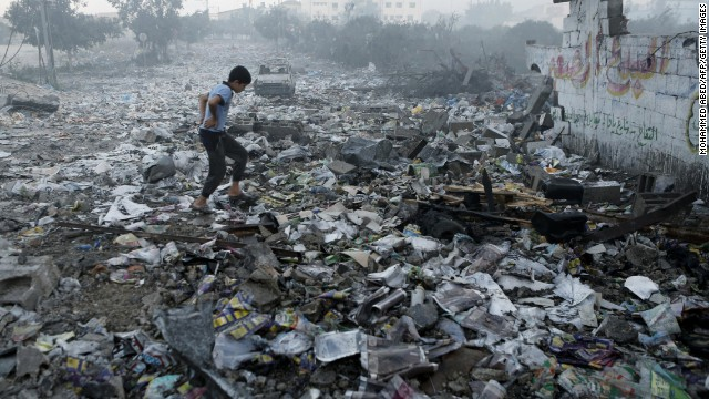 A Palestinian youth walks on debris as he inspects damages following an Israeli air strike in Gaza City, on July 24, 2014. Fifteen Palestinians were killed today when an Israeli shell slammed into a UN shelter where hundreds of civilians had taken refuge, sending the death toll in Gaza soaring to 788 despite world efforts to broker a ceasefire.