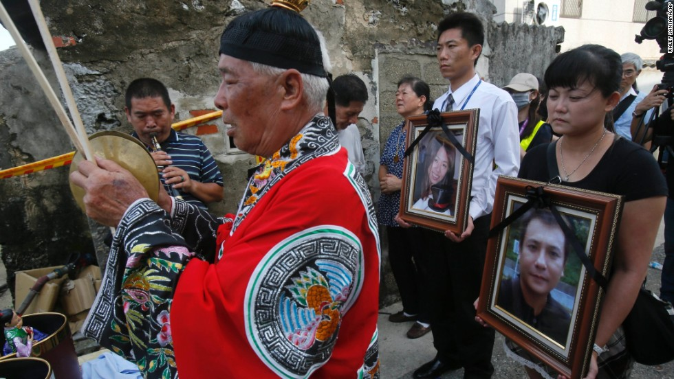 Relatives of victims pray with the victims' portraits during a makeshift ceremony at the crash site on the outlying island of Penghu, Taiwan, on July 24. Stormy weather on the trailing edge of Typhoon Matmo was the likely cause of the plane crash, the airline said Thursday.