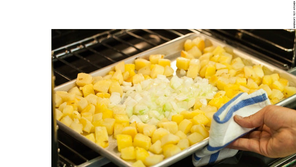 10. Clear about 8 by 5-inch space in center of baking sheet and add onion mixture. Roast for 15 minutes. Scrape and turn again, mixing onions into potatoes. Continue to roast until potatoes are well browned and onions are softened and beginning to brown, 5 to 10 minutes.