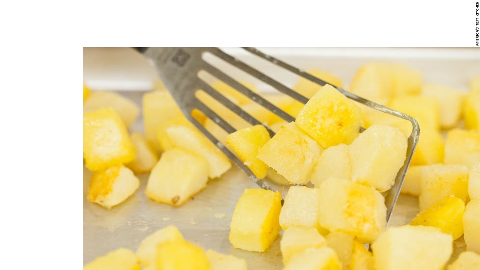 8. While potatoes roast, combine onions, remaining 1 tablespoon vegetable oil, and 1/2 teaspoon kosher salt in bowl. Remove baking sheet from oven.