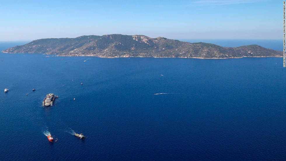 Tugboats tow the wreck of the Costa Concordia as it leaves Italy's Giglio Island on Wednesday, July 23.