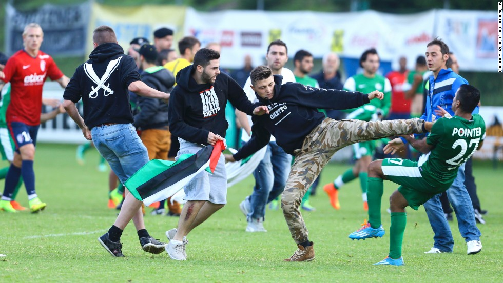 A Palestinian supporter kicks a member of the Israeli soccer team Maccabi Haifa on Wednesday, July 23, after protesters snuck onto the field during a preseason match against French club Lille OSC in Bischofshofen, Austria.