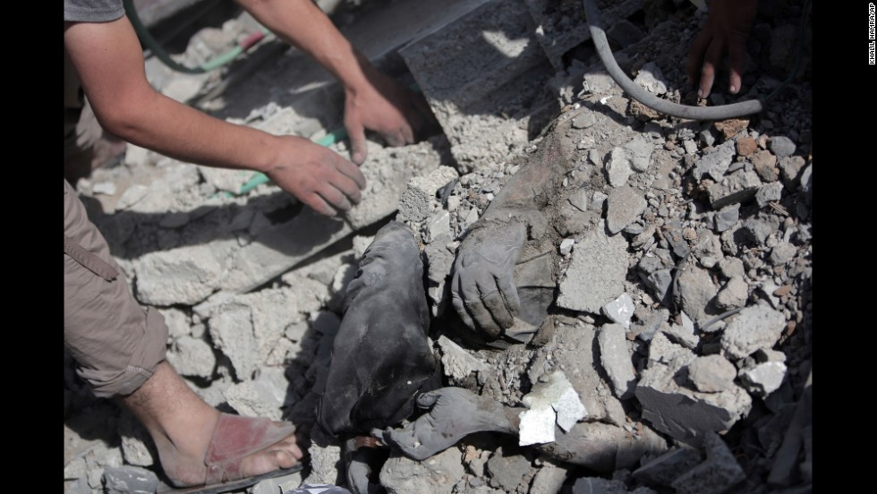 Palestinians dig a body out of the rubble of a destroyed house in Gaza during the cease-fire on July 26.