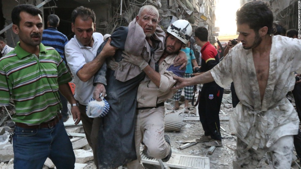 People carry an injured man away from the site of an airstrike, reportedly carried out by Syrian government forces, in Aleppo on Sunday, July 27.